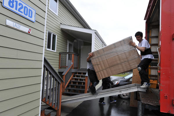 Two men loading furniture onto a moving truck.