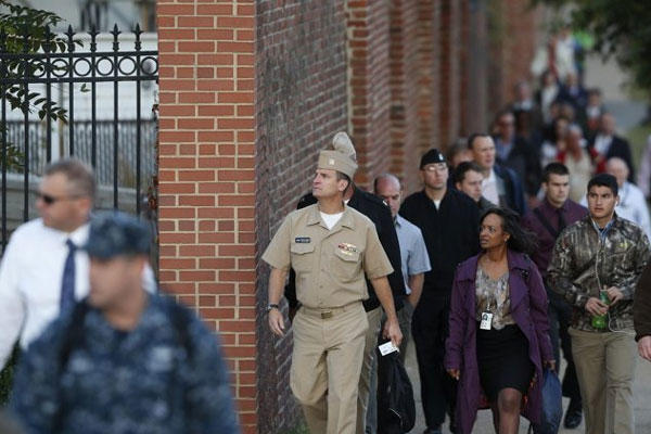 Military personnel and workers walk along the perimeter of the Washington Navy Yard Thursday, Sept. 19, 2013.