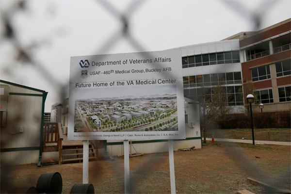 In this Thursday, April 2, 2015 file photo, and seen through the criss-cross pattern of a cyclone fence, the sign marking construction stands at the site of the Veterans Affairs hospital in Aurora, Colo.  (AP Photo/David Zalubowski, file)