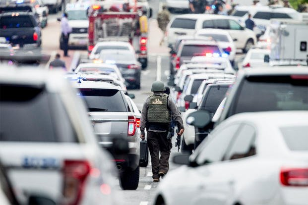 A large police presence gathers along M St. in Southeast Washington, Thursday, July 2, 2015, after an official said shots have been reported in a building on the Washington Navy Yard campus. (AP Photo/Andrew Harnik)