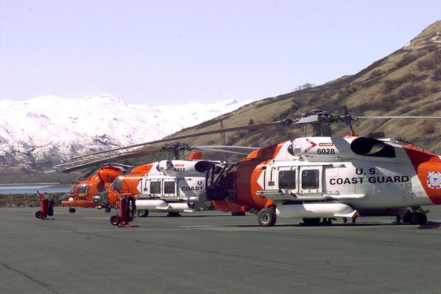 Two Coast Guard HH-60J helicopters and one HH-65A helicopter sit on the tarmac of Air Station Kodiak awaiting the next call for help. (U.S. Coast Guard photo by PAC Tod A. Lyons, USCG)