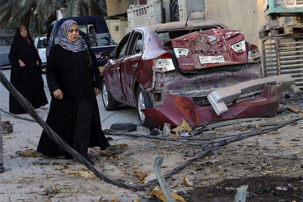 In this Oct. 8, 2013 file photo, women walk past the aftermath of a car bomb attack in the mainly Shiite neighborhood of Zafaraniyah in southeastern Baghdad, Iraq.