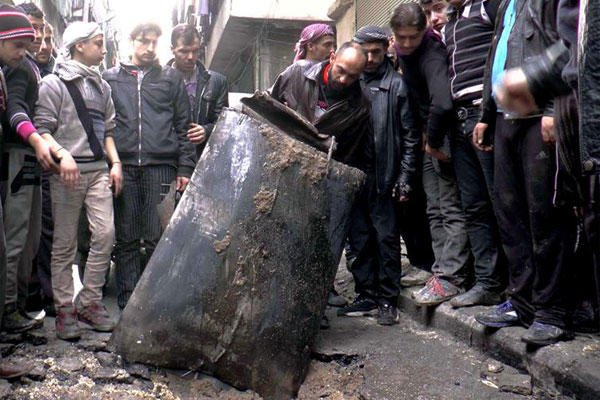 In this Jan. 19, 2014, file photo provided by Aleppo Media Center (AMC) Syrian citizens inspect an unexploded barrel of explosives which was dropped from a Syrian forces helicopter, on a street in Aleppo, Syria.