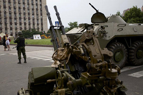 A Pro-Russian militia member guards next to an APC and anti-aircraft gun, outside the administrational building in Donetsk, Ukraine, on Thursday, May 29, 2014. (AP Photo/Ivan Sekretarev)