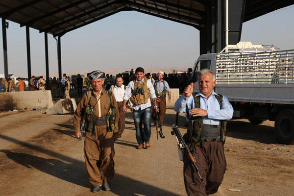Kurdish Peshmerga fighters walk toward the front line with militants from the extremist Islamic State group, at the Khazer checkpoint outside of the city of Irbil in northern Iraq, Friday, Aug. 8, 2014 (AP Photo/Khalid Mohammed)