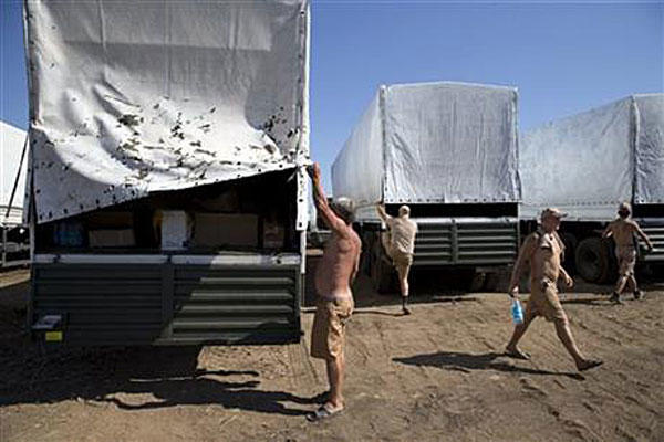 Drivers prepare to show cargos to journalists in a field where the aid convoy is parked near the Ukrainian border on Friday, Aug. 15, 2014. Pavel Golovkin/AP