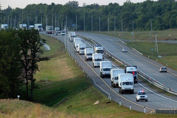 A convoy of white trucks carrying humanitarian aid passes along the main road M4 (Don highway) Voronezh region, Russia, Tuesday, Aug. 12, 2014 (Pavel Golovkin/AP)
