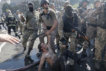 Special forces police battalion officers detain an activist during a clash in Independence Square in Kiev, Ukraine, Thursday, Aug. 7, 2014. Efrem Lukatsky/AP
