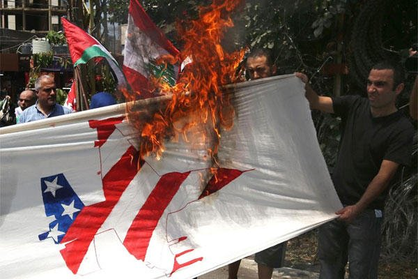 Supporters of Lebanese and Palestinians Communist groups burn a banner depicting an American jet plane during a protest against the Israeli offensive, near the U.S. Embassy in Aukar, east of Beirut, Lebanon, Sunday July 20, 2014. (AP)