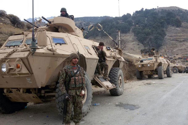 In this Dec. 24, 2014 photo, Afghan National Army soldiers stand guard near their vehicle during an ongoing operation in the Dangam district of Kunar province, Afghanistan. (AP Photo)
