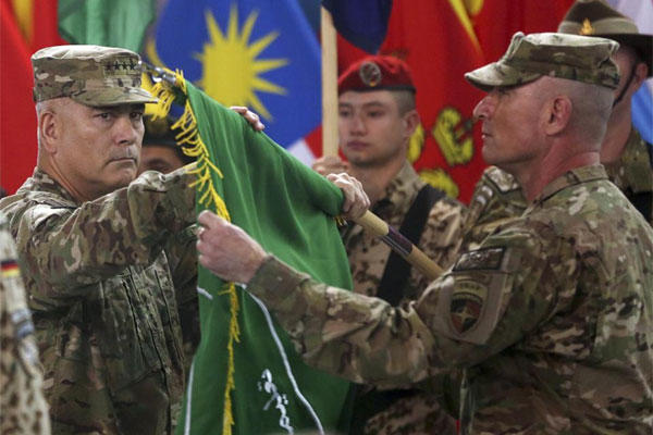 "Commander of ISAF, Gen. John Campbell, left, and Command Sgt. Maj. Delbert Byers open the ""Resolute Support"" flag during a ceremony at the ISAF headquarters in Kabul, Sunday, Dec. 28, 2014. (AP Photo/Massoud Hossaini)"