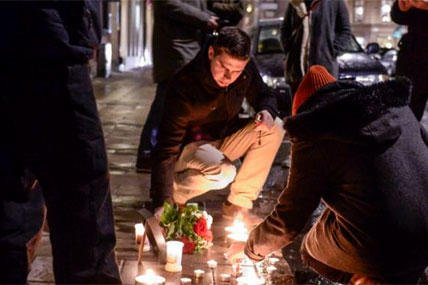 People light candles to support the victims of the terror attack, in Paris, outside the French embassy in Stockholm, Wednesday, Jan. 7, 2015 (AP Photo/TT News Agency, Claudio Bresciani)