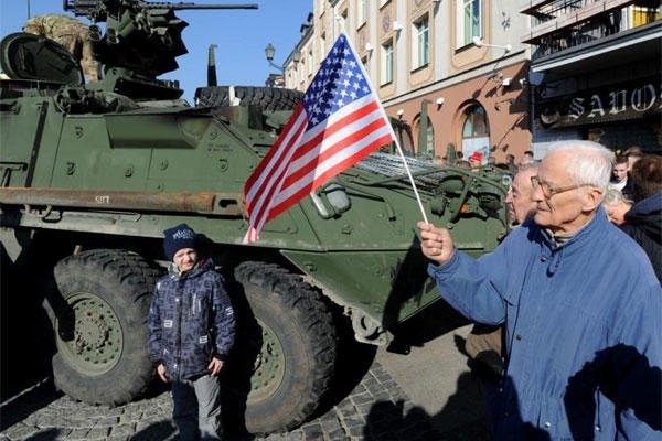 A man holding a US flag walks past a US Army Stryker from the 3rd Squadron of the 2nd Cavalry Regiment, during their stop to meet local residents in Bialystok, Poland, Tuesday, March 24, 2015. (AP Photo/Alik Keplicz)
