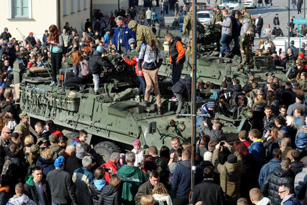 People surround a group of US Army Strykers from the 3rd Squadron of the 2nd Cavalry Regiment, during a stop in Bialystok, Poland, Tuesday, March 24, 2015. (AP Photo/Alik Keplicz)