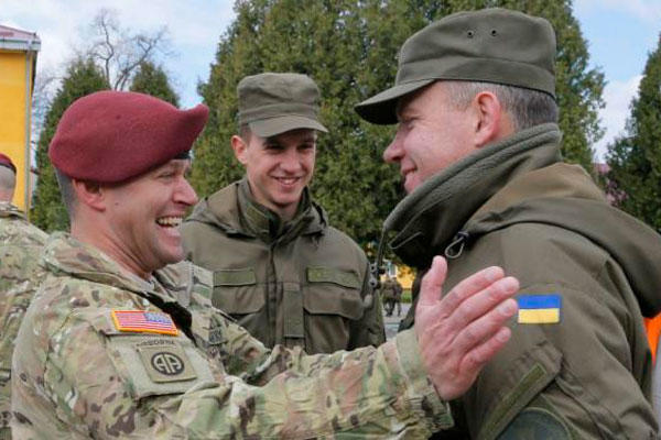 US and Ukrainian soldiers talk during the opening ceremony of the 'Fiarles Guardian - 2015', in the Lviv region, western Ukraine, Monday, April 20, 2015. (AP Photo/Efrem Lukatsky)