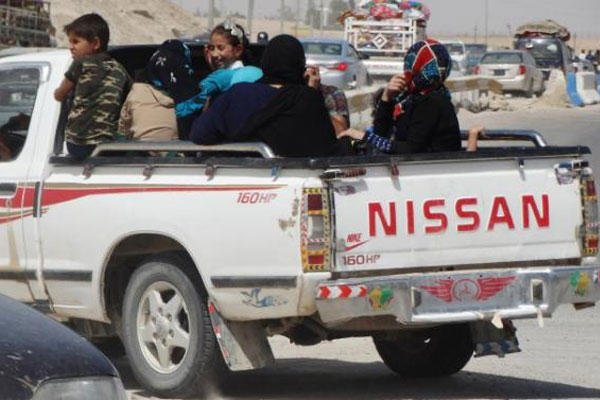 In this Monday, May 18, 2015 photo, civilians fleeing Ramadi, Iraq drive away a police checkpoint as they drive through Habaniyah town, 80 kilometers (50 miles) west of Baghdad (AP Photo)