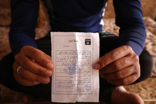 "In this Wednesday, May 27, 2015 photo, Salim Ahmed holds the ""repentance card"" he received from the Islamic State group in June 2014 shortly after the militants took over his home village of Eski Mosul in northern Iraq. (AP Photo/Bram Janssen)"