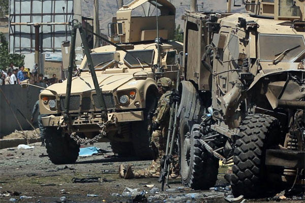 Armored vehicles remain at the site of a blast targeting the NATO convoy in Kabul, Afghanistan, Tuesday, June 30, 2015 (AP Photo/Massoud Hossasini)