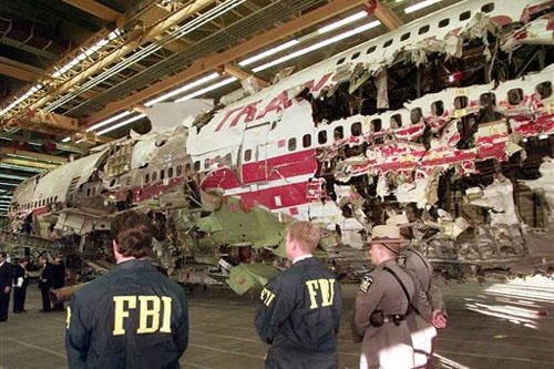 FILE - In this Nov. 19, 1997 file photo, FBI agents and New York state police guard the reconstruction of TWA Flight 800 in Calverton, N.Y. AP Photo