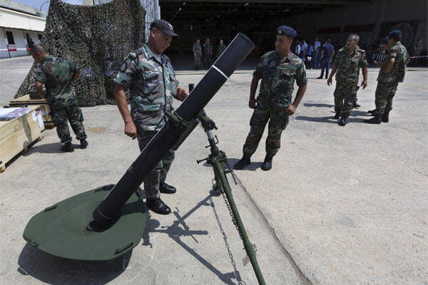 Lebanese army soldiers look at a mortar at the Rafik Hariri International Airport in Beirut, Lebanon, Friday, Aug. 29, 2014. (AP Photo/Bilal Hussein)