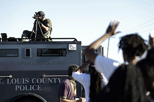 A member of the St. Louis County Police Department aims at protesters in Ferguson, Mo. Police in riot gear and military garb have clashed nightly with protesters since the shooting of Michael Brown and trained weapons from armored trucks. Jeff Roberson/AP