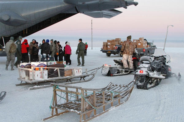 This photo taken Dec. 6, 2014, shows Christmas toys and other supplies being loaded from a C130 military transport plane onto sleds being pulled by snowmobiles in Shishmaref, Alaska. (MARK THIESSEN/AP)