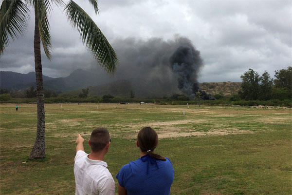 In this May 17, 2015 photo, a man and woman look toward smoke rising from a Marine Corps Osprey aircraft after making a hard landing on Bellows Air Force Station near Waimanalo, Hawaii. (Zane Dulin via AP)