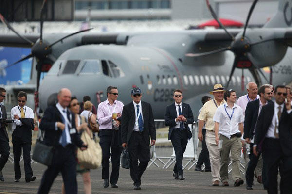 People walk around on day four of the Farnborough International Airshow on July 16, 2014, in Farnborough, England. The show is the biggest event of its kind and attracts people from all over the world. (Getty Images)
