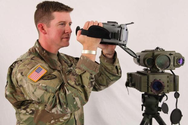 Maj. Robert J. Heatherly, holds a new Joint Effects Targeting System next to the current, tripod mounted Lightweight Laser Designator Rangefinder. (Army Photo)