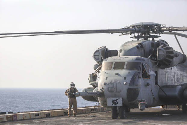 A U.S. Marine stands by a CH-53E Super Stallion helicopter aboard the amphibious transport dock ship USS San Antonio during a transit through the Strait of Hormuz on Oct. 8, 2016. (U.S. Marine Corps photo/Sgt. Ryan Young)