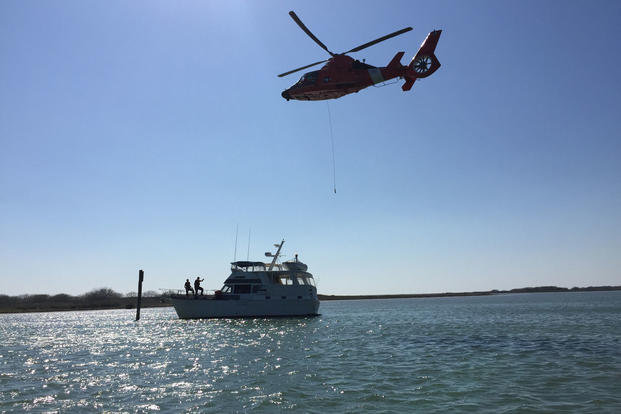 A Coast Guard Air Station Corpus Christi MH-65 Dolphin helicopter crew lowers a dewatering pump to a 44-foot yacht taking on water with six people aboard near the Port Mansfield Jetties off Texas, Jan. 31, 2016. (U.S. Coast Guard photo)