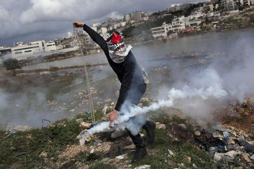 A masked Palestinian throws back a gas canister fired by Israeli forces during a protest to support Palestinian prisoners outside Ofer, an Israeli military prison near the West Bank city of Ramallah, Tuesday, Feb. 19, 2013.(AP Photo/Bernat Armangue)