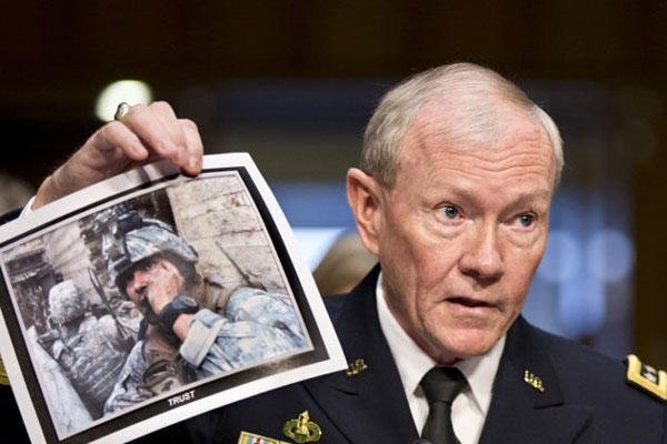 Gen. Martin Dempsey, chairman of the Joint Chiefs of Staff, holds up a photo of a deployed American soldier as he testifies before the Senate Armed Services Committee at his reappointment hearing, on Capitol Hill in Washington, Thursday, July 18, 2013.