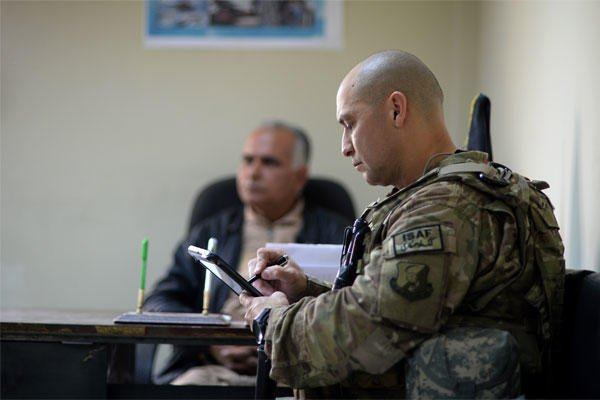 Senior Master Sgt. Carmelo Vega Martinez takes notes during a meeting with Afghan Air Force recruiters, Feb. 25, 2014, Kabul, Afghanistan.