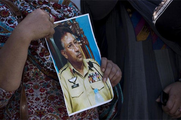 A supporter of former Pakistani President Pervez Musharraf holds a photo of him outside the special court in Islamabad, Pakistan, Monday, March 31, 2014. (AP Photo/B.K. Bangash)