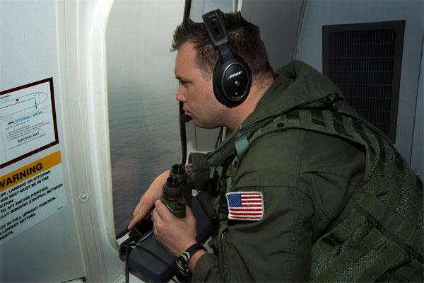 Chief Naval Aircrewman (Operator) Samuel Judd, assigned to Patrol Squadron (VP) 16, searches out the window of a P-8A Poseidon while flying over the Indian Ocean in support of the international effort to locate Malaysia Airlines flight MH370.