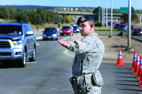 A 10th Security Forces Squadron Airman directs traffic through the Academy's north gate to Falcon Stadium for the Air Force vs. Notre Dame football game Oct. 26, 2013. (Air Force photo)