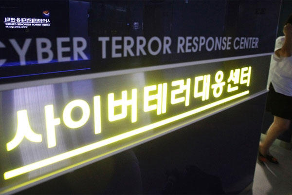 In this July 16, 2013 file photo, a woman walks by a sign at Cyber Terror Response Center of National Police Agency in Seoul, South Korea. (AP photo)