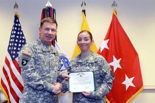 Lt. Gen. James C. McConville, the Army's deputy chief of staff for personnel, presents 1st Sgt. Katrina Moerk with the citation for her Army Commendation Medal. (U.S. Army Photo)