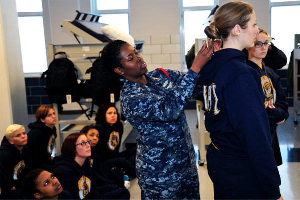 Chief Logistics Specialist Natali Philip, a recruit division commander, uses a ruler to measure the hair of Seaman Recruit Briana Cochems to show proper hair grooming standards to new recruits. (U.S. Navy Photo by Lt. Adam Demeter/Released)