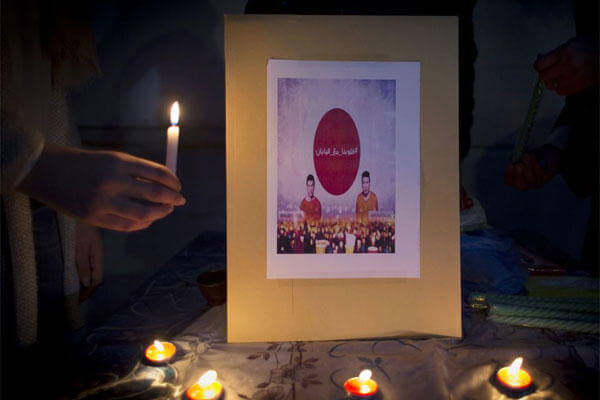 Jordanians hold candles during a candle vigil in support of Japan, in front of the Japanese embassy, in Amman, Jordan, Monday, Feb. 2, 2015. (AP Photo/Nasser Nasser)