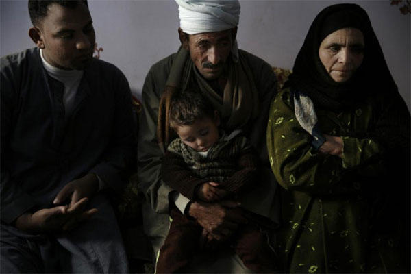 In this Feb. 14, 2015 photo, family members of abducted Coptic Christian Malak Ibrahim, one of 21 Coptic Egyptian men seized by Islamic State militants in the central city of Sirte, Libya sit at home in the village of el-Aour. (AP Photo/Hassan Ammar)