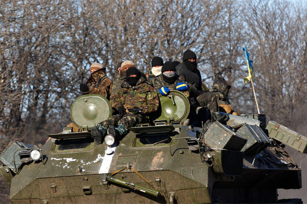 Ukrainian government soldiers sit on top of their armored vehicle driving on a road stretching away from the town of Artemivsk, Ukraine, towards Debaltseve, Tuesday, Feb. 17, 2015. (AP Photo/Petr David Josek)