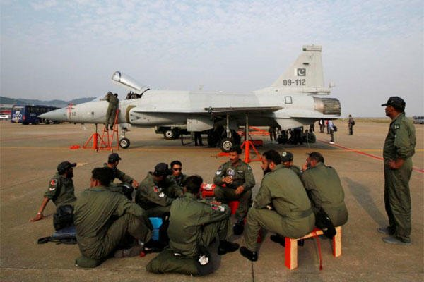 In this Nov. 21, 2010, file photo, Pakistan Air Force personnel sit in front of their JF-17 jet fighter at the 8th China International Aviation and Aerospace Exhibition in Zhuhai, southern coast of Guangdong province, China. (AP Photo/Kin Cheung, File)