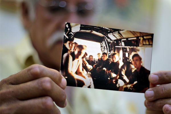 In this April 28, 2015 photo, former U.S. Marines Master Gunnery Sgt. Juan Valdez holds a photo of himself, rear center, sitting on the last helicopter leaving the U.S. Embassy in Saigon on April 30, 1975, in Ho Chi Minh City. (AP Photo/Dita Alangkara)