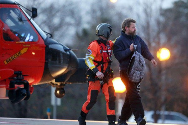 Louis Jordan, right, walks from the Coast Guard helicopter to the Sentara Norfolk General Hospital in Norfolk, Va., after being found off the North Carolina coast, Thursday, April 2, 2015. (AP Photo/The Virginian-Pilot, Steve Earley)