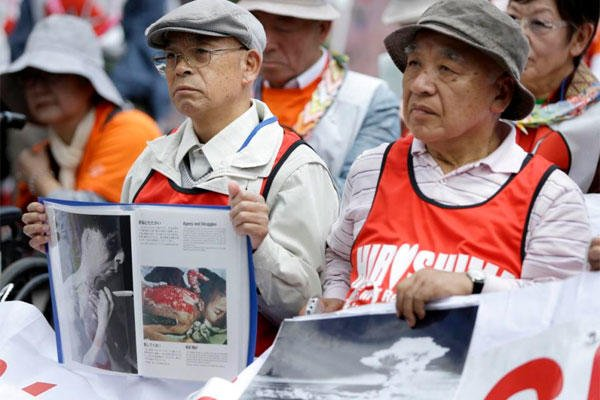 Survivors of the nuclear attacks on Japan in 1945 hold photographs during an anti-nuclear rally in Union Square in New York, Sunday, April 26, 2015. (AP Photo/Seth Wenig)