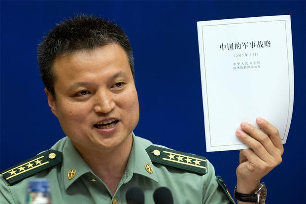 China's Defense Ministry spokesman Yang Yujun holds up a report on China's Military Strategy during a press conference at the State Council Information Office in Beijing, China, Tuesday, May 26, 2015. (AP Photo/Andy Wong)