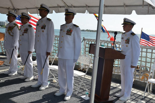 Coast Guard Cmdr. Craig J. Wieschhorster and Cmdr. Adam B. Morrison stand at attention during the change of command ceremony for the Coast Guard Cutter Mohawk in Key West, Fla., July 2, 2015. (U.S. Coast Guard photo)