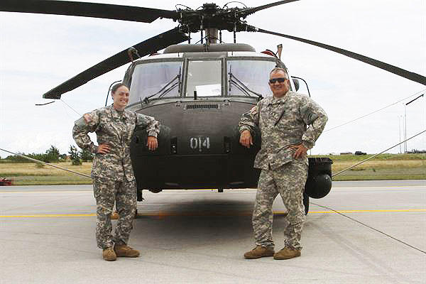 New York Army National Guard members Warrant Officer Meghan Polis, left, and Chief Warrant Officer 3 Stephen Polis pose in front of a UH-60 Black Hawk helicopter at Fort Drum, New York, July 22, 2015. (U.S. Army photo by Sgt. Jonathan Monfiletto)
